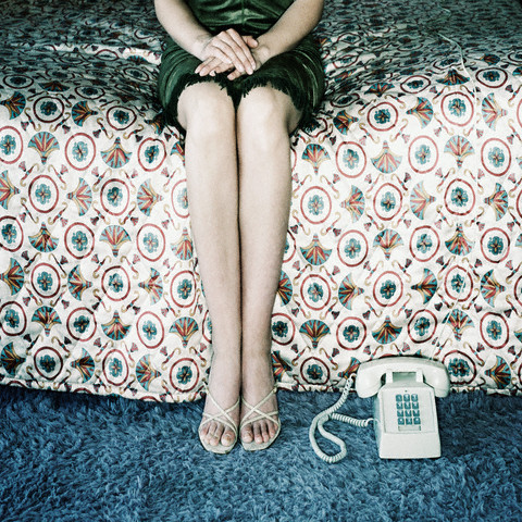 Woman Waiting for Phone to Ring --- Image by © Dennis Galante/CORBIS